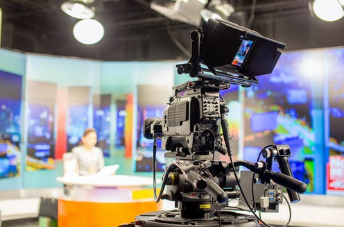 TV studio with camera and woman news presenter
