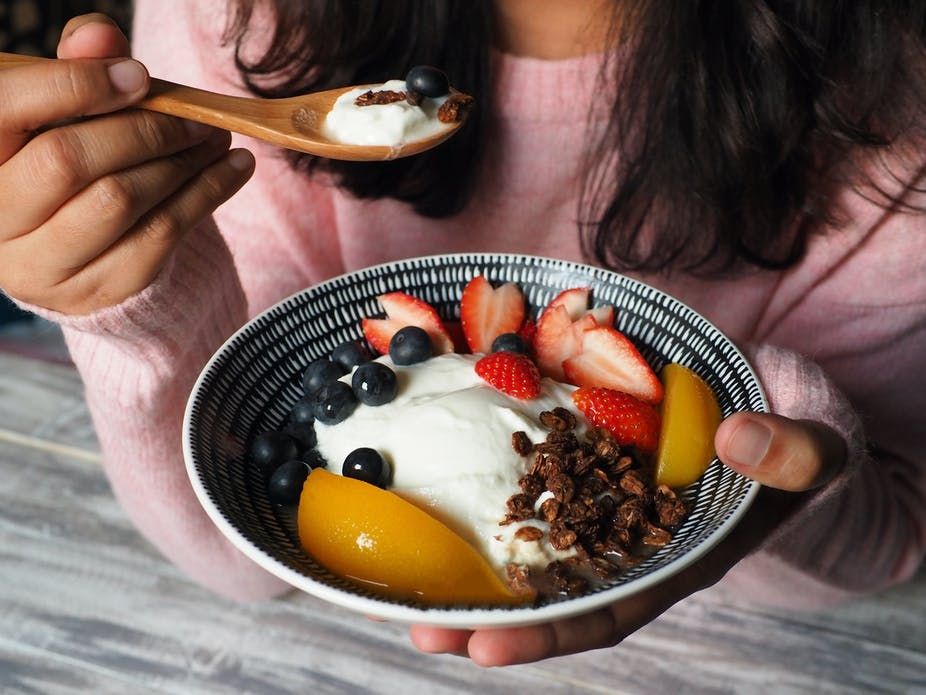 Woman hold bowl of yoghurt and fruit and puts spoon to her mouth.