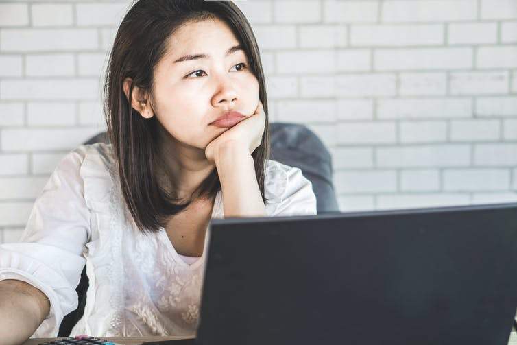A woman stares forlornly at her laptop.