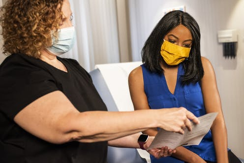 Doctor in a mask shows patient a pamphlet.