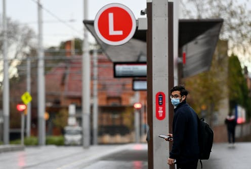 A man waiting at a light rail stop in Sydney wearing a mask.