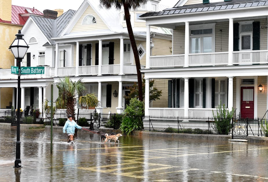 A woman in rain boots walks two dogs through shin-high water in the street past old houses with large porches on South Battery in Charleston