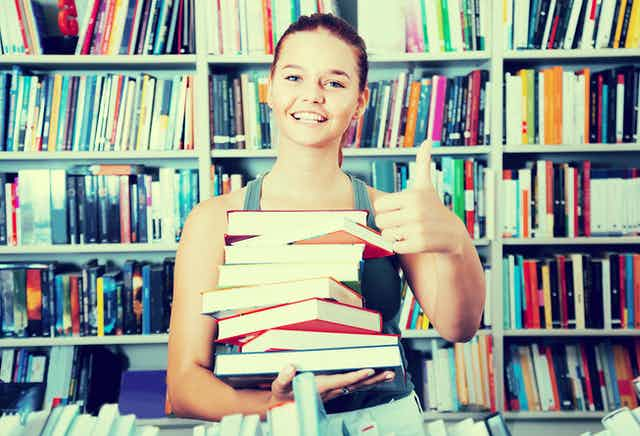 Teen girl holding a stack of books in front of a book shelf.