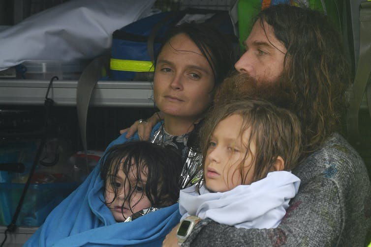 man, woman and two children in blankets