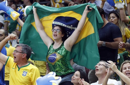 A woman in a Brazilian flag printed top waves a Brazil flag at the Rio Olympics, surrounded by other fans