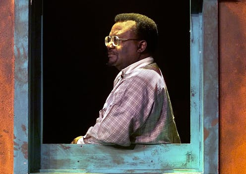 A man in checked shirt stands in profile, leaning his arm on a window frame. He wears glasses and is dramatically lit with what appears to be stage light.