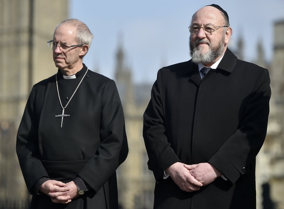 Britain's Archbishop of Canterbury Justin Welby (L) and Chief Rabbi of the United Hebrew Congregations of the Commonwealth Ephraim Mirvis (R) attend a vigil in the grounds of Westminster Abbey