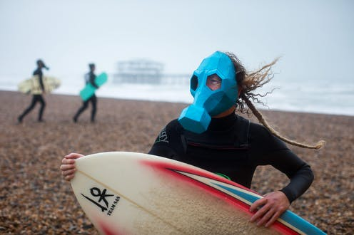 A surfer wearing a gas mask on a shingle beach.