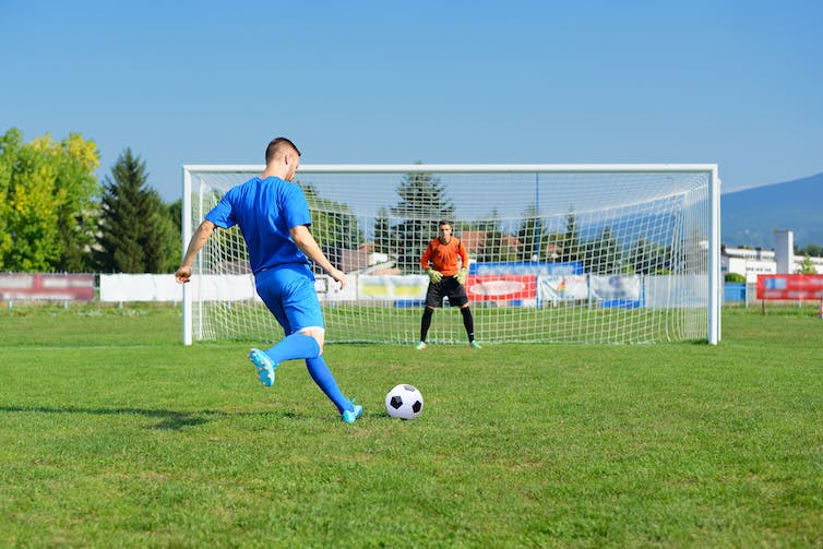 A football player takes a penalty kick, while the goal waits in the net to stop it.