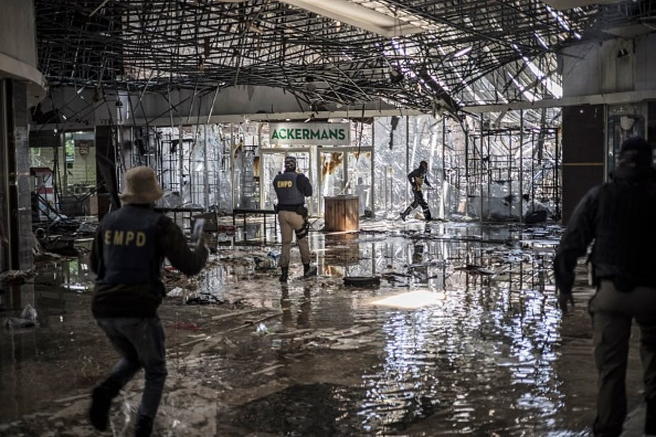 Interior of a building with damaged ceiling and water on the floor; people wearing police bulletproof vests