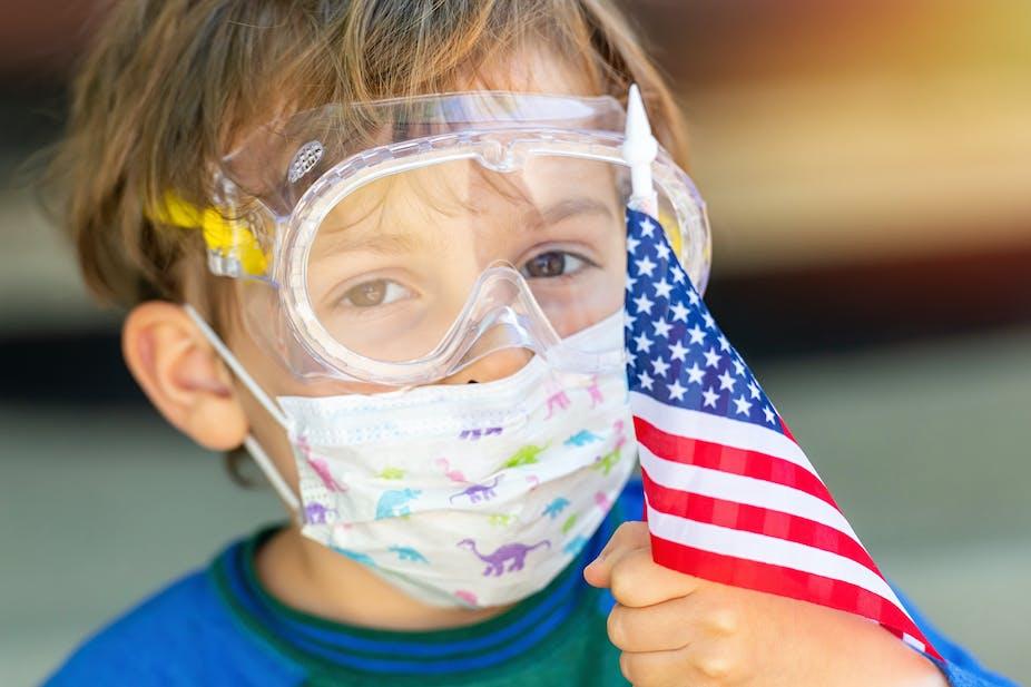 Boy wears protective mask, holds U.S. flag