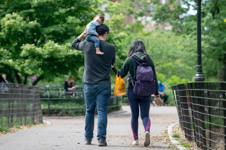 A man, woman and baby walk through a park together