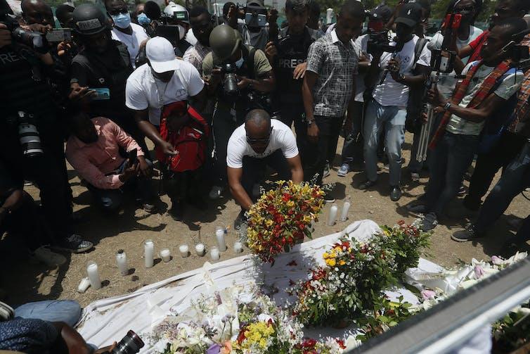 Un homme dépose des fleurs alors qu'une foule s'est réunie autour d'un autel rendant hommage au président assassiné