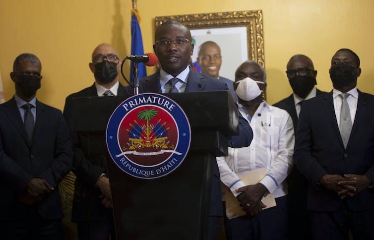 Le premier ministre intérimaire Claude Joseph donne une conférence de presse à Port-au-Prince, le 13juillet 2021. Une photo de feu le président haïtien Jovenel Moise, qui a été assassiné à son domicile le 7juillet, est accrochée au mur derrière