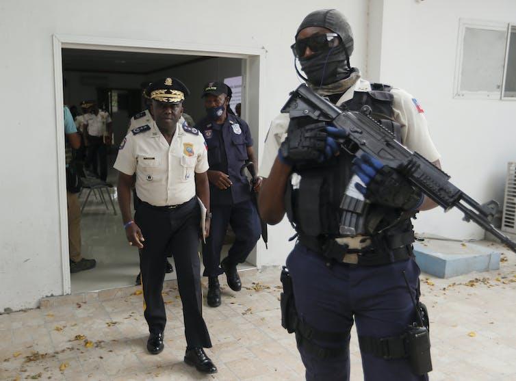Leon Charles, à gauche, directeur général de la police haïtienne, quitte une salle après une conférence de presse au siège de la police à Port-au-Prince
