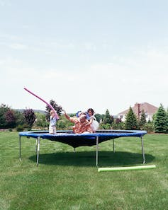 A family on a trampoline with the trampoline stretching down toward the ground.