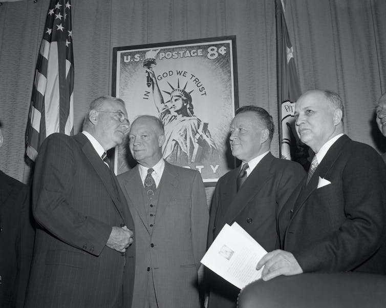 President Eisenhower at a ceremony introducing a 8-cent Statue of Liberty stamp with the inscription 'In God We Trust.'