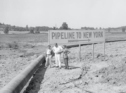 Three men next to a bend in a large pipeline.