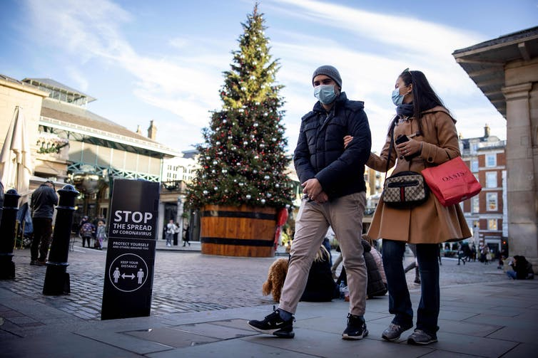 masked people walk past a public Christmas tree