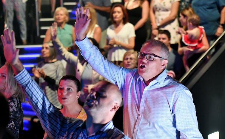 Man raises arm as he sings during a church service
