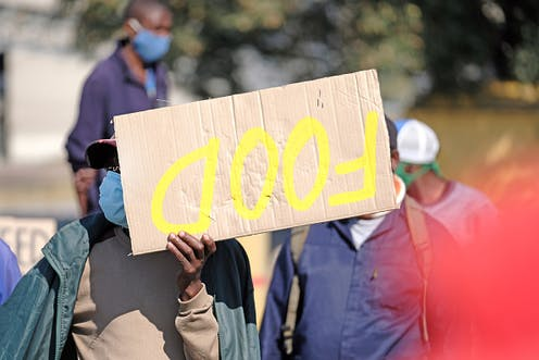 """Person holding up a placard that reads """"Food"""""""