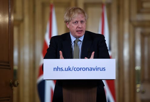Prime Minister Boris Johnson stands at a podium with a placard reading nhs.uk/coronavirus