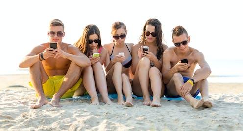 Cinco adolescentes sentados en la playa, en bañador y con gafas de sol, mirando sus teléfonos móviles.