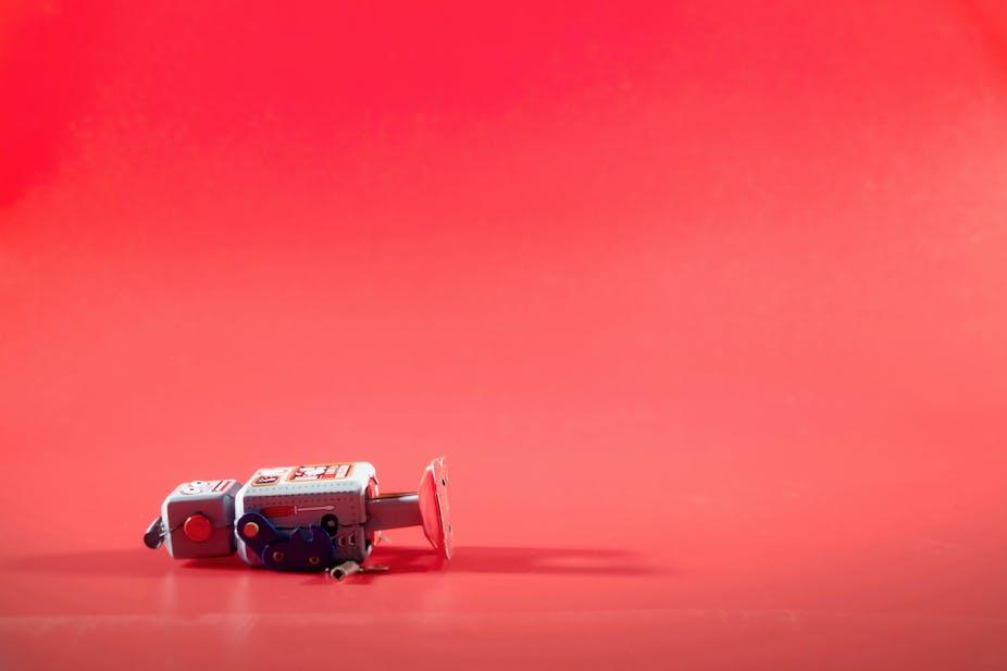 Broken robot against a red background
