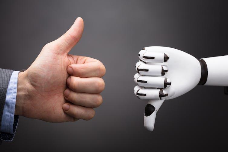 Businessman thumb up, robot thumb down