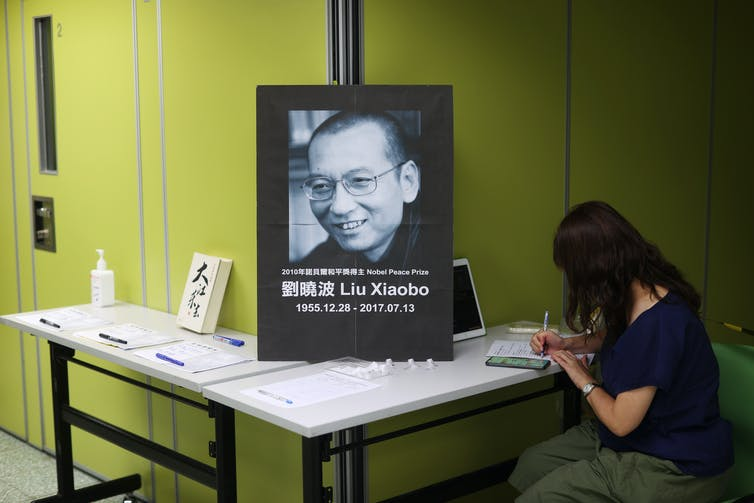 A woman writes in a book of condolences in front of a portrait of deceased Chinese democracy activist Liu Xiaobo, Hong Kong, 2020.