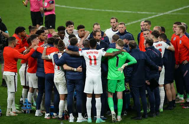 The whole England teams huddles.