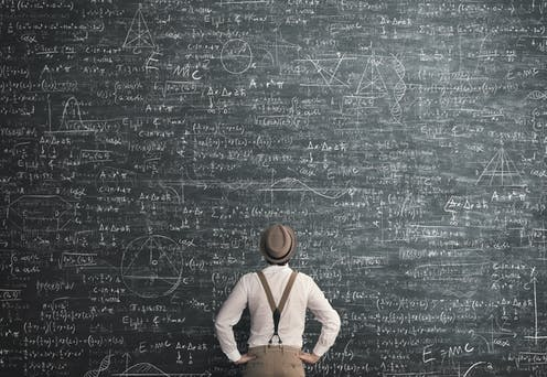 A man consults a large blackboard of equations