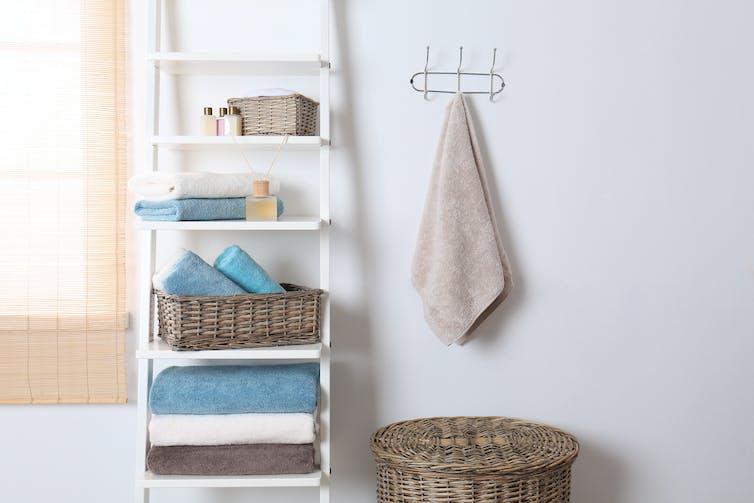 A bathroom hand towel hanging next to a shelving unit.