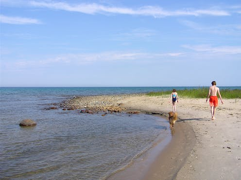 Two people walk along a spit of sand.