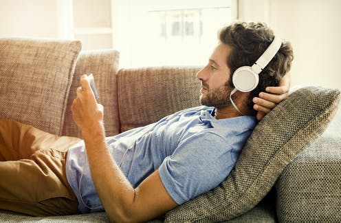 A man relaxing on a couch with headphones on, watching a video on his phone