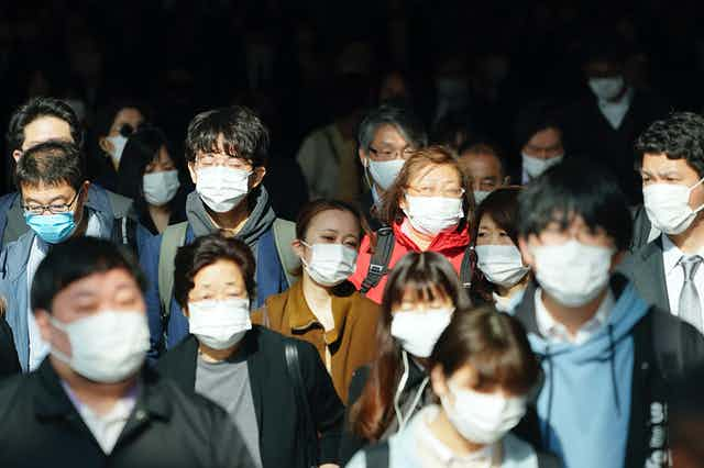 Crowd of people wearing medical face masks.