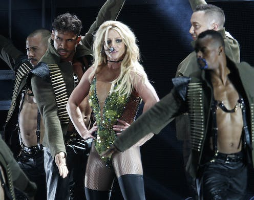 Britney Spears wears a tight-fitting sequined green dress next to four male dancers as she performs a concert in Taipei in 2017