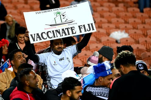 Rugby fan holdin sign saying 'vaccinate Fiji'