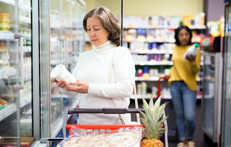 Woman in supermarket looks at the packaging of a yoghurt container.