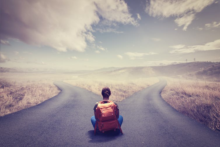 Girl with backpack sitting in front of a road that splits into two.