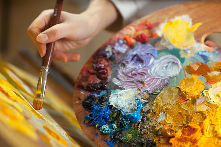 Artist's palette with lots of colourful paint.