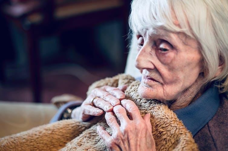 older woman clutches blanket