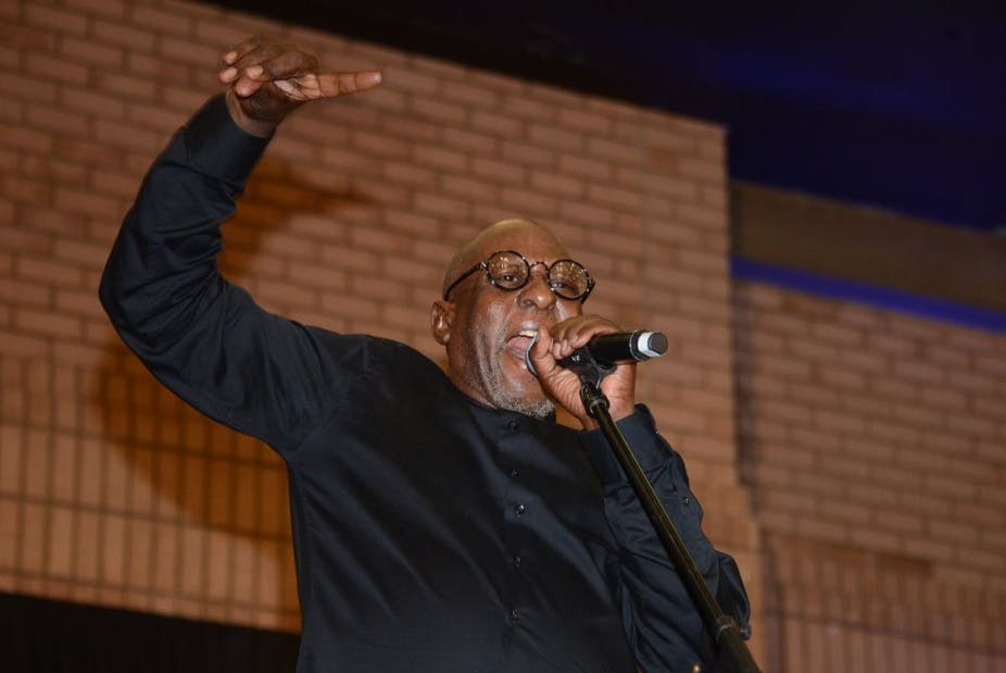 An elderly man on stage singing heartily into a microphone, a hand raised above his head.