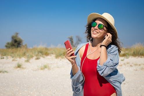 Una mujer en la playa escuchando un audio a través del móvil.