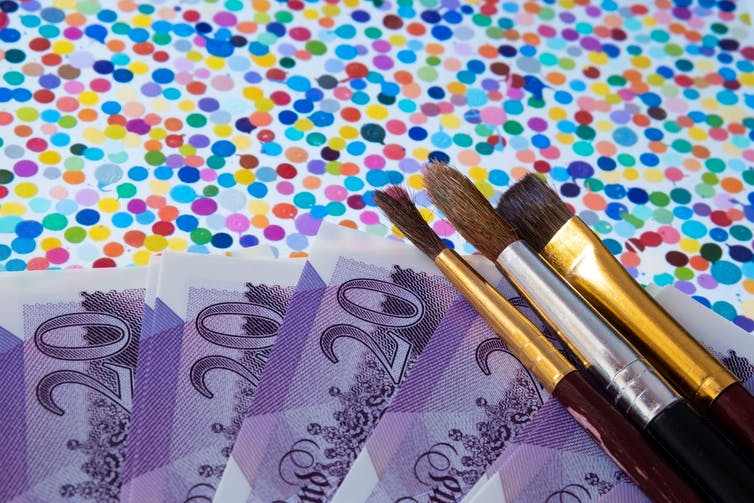 Damien Hirst's The Currency overlaid with paintbrushes and twenty pound notes