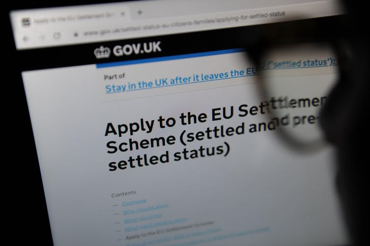 A person in silhouette looking at the webpage for the EU settlement scheme application.