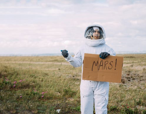 Man in astronaut suit holds up cardboard sign reading 'MARS!' on the side of the road.