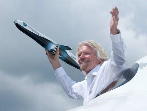 Richard Branson clutching a model Virgin Galactic spaceplane.