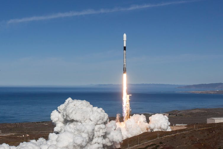 A rocket blasting off from a coastal launch site.