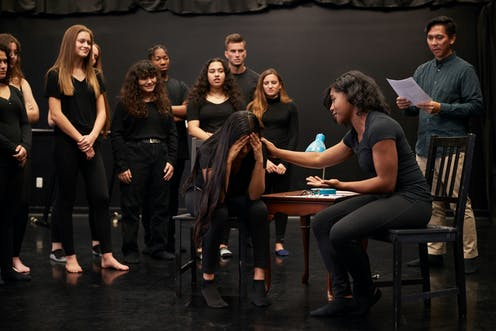 A group of drama students dressed in black take part in an improv class